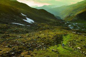 Zwei Mountainbiker fahren auf einem Singletrail durch ein einsames Tal, auf dem Weg nach Livigno beim der Trailtour Ischgl-Livigno