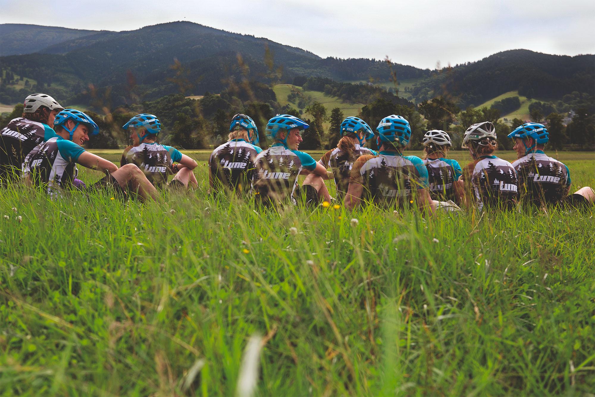 Das beitune Team sitzt auf einer grünen Wiese und blickt auf die Schwarzwaldgipfel.